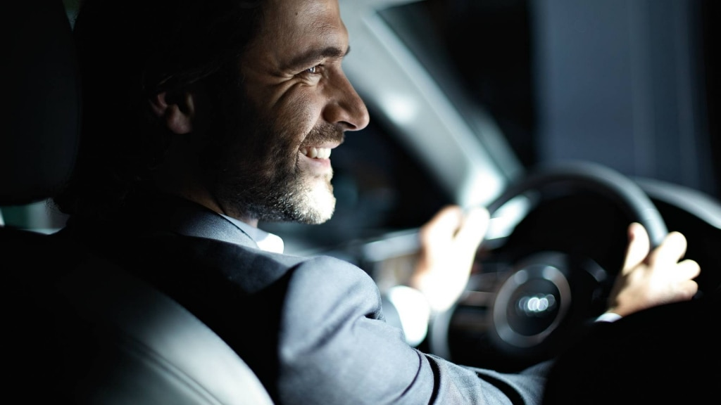 A smiling man sits in an Audi, firmly grasping the wheel.