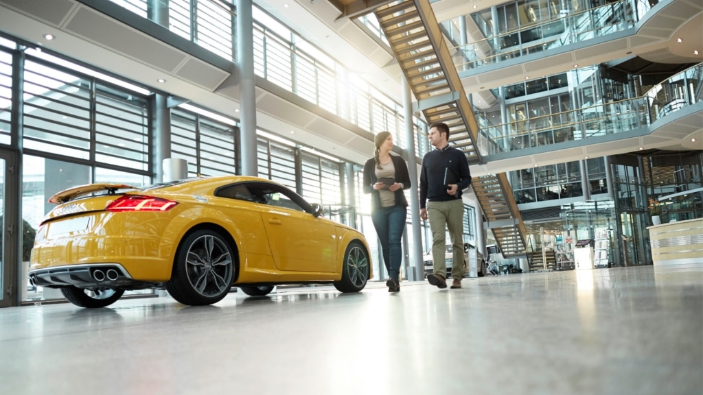 A man and woman walk past a yellow Audi TT RS engaged in a lively conversation.